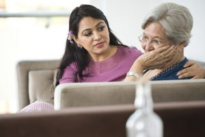 This image shows a young woman supporting her elderly mother as her mother talks to her about experiencing financial abuse and investment fraud.