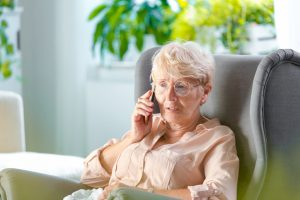This image shows an older adult talking to someone she trusts on the phone about financial abuse that she is experiencing, and where to report it.