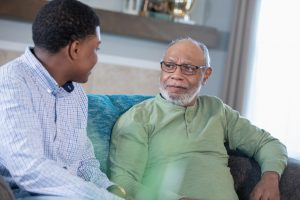 This photo shows a young man sitting down with his grandfather in a safe and comfortable environment to talk to him about elder financial abuse and investment fraud.