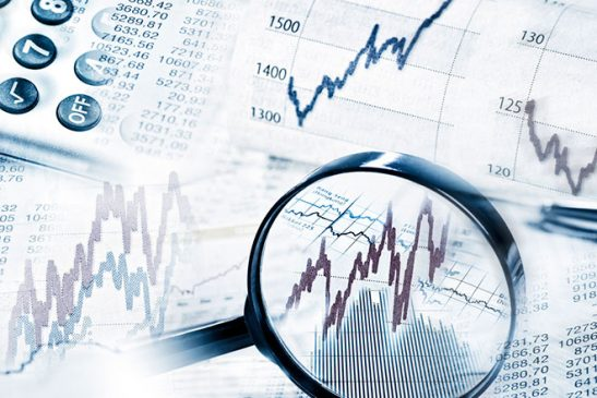 This image of a magnifying glass looking at the highs and lows of a financial chart represents stock market volatility that we have seen during the COVID-19 pandemic so far.