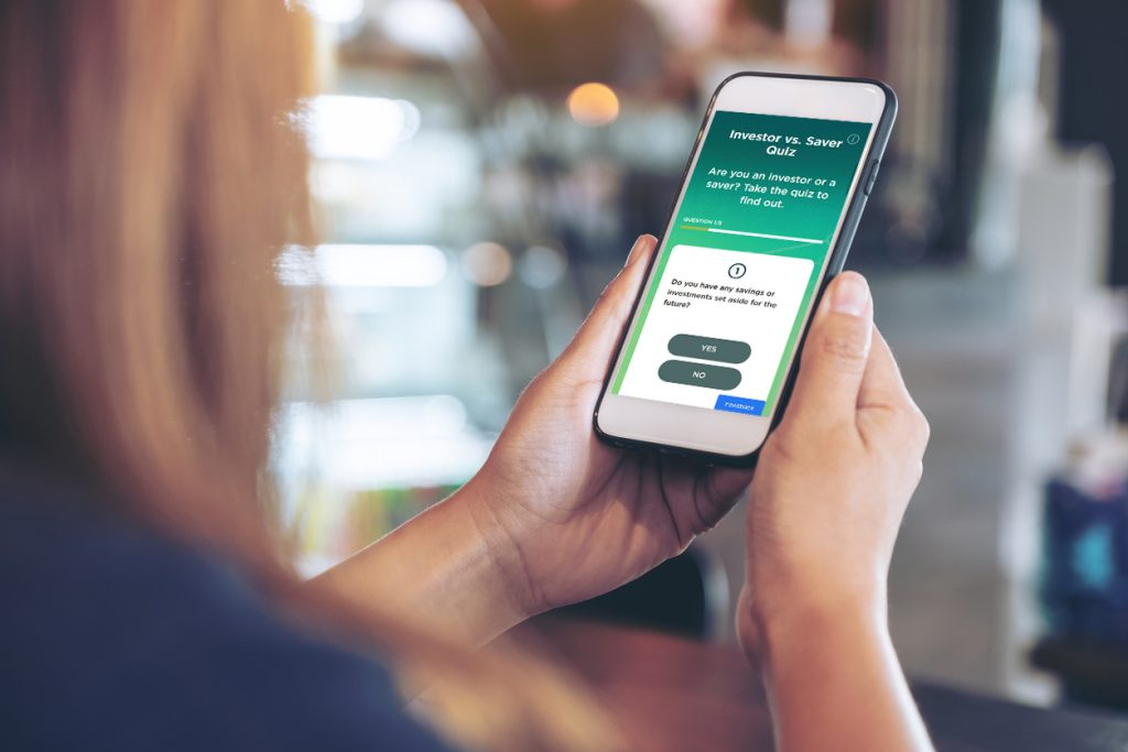 The purpose of this image of a woman holding her smartphone is to show British Columbians what the BCSC InvestRight Investor vs. Saver Quiz looks like, and how easy it is to access on any smart device.