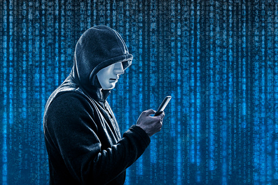 This image of a masked person holding a smartphone with a cryptic blue background represents the possibility that digital wallets can be hacked and the hacker can gain access to crypto-assets stored within the wallet.