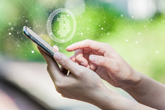 This image of a person typing on their smartphone with a Bitcoin icon floating above it represents the popularity of certain cryptocurrencies like Bitcoin, Bitcoin cash, and Litecoin, and how it's important to do your research before committing to any crypto-asset investment.