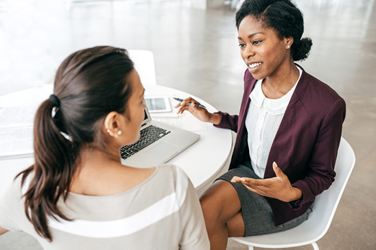 A young woman meets with a registered investment advisor to discuss her financial goals and to create an investment strategy according to her risk tolerance and time horizon.